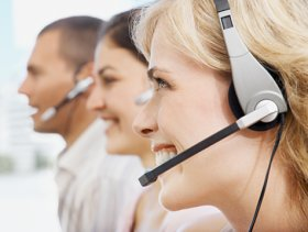 Young woman working in call centre, smiling, profile, close-up
